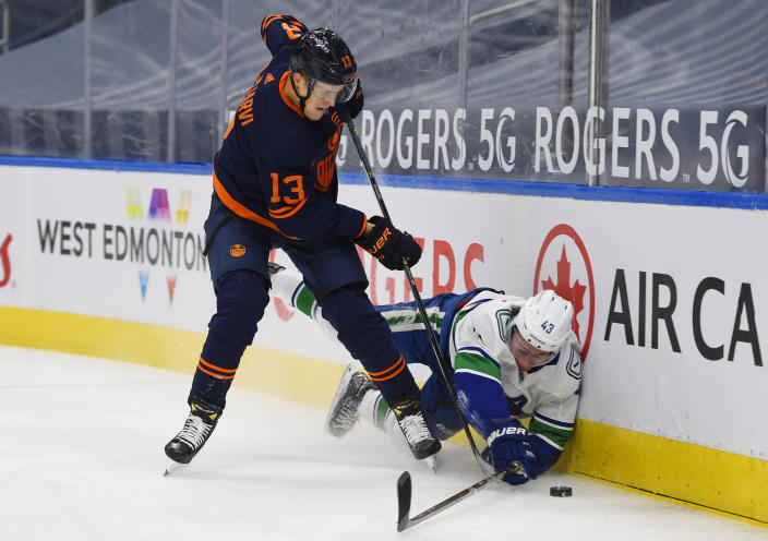 Edmonton Oilers' Jesse Puljujarvi (13) checks Vancouver Canucks' Quinn Hughes (43) during the second period of an NHL hockey game Wednesday, Jan. 13, 2021, in Edmonton, Alberta. (Dale MacMillan/The Canadian Press via AP)