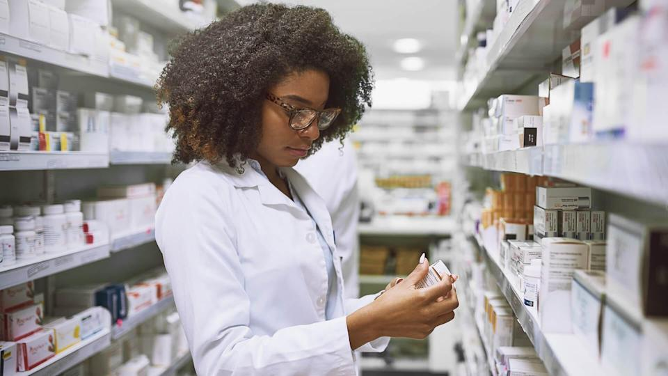 Shot of a focused young female pharmacist walking around and doing stock inside of a pharmacy.