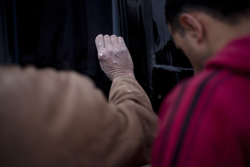"""A Palestinian worker with paint marks on his hand boards a Palestinian-only bus on route to the West Bank in Tel Aviv area , Israel, Monday, March 4, 2013. Israel's decision to launch a pair of """"Palestinian-only"""" bus lines in the West Bank condemned by critics as racism and hailed by Israel as a goodwill gesture have shined a light on the messy situation created by 45 years of military occupation and Jewish settlements.. (AP Photo/Ariel Schalit)"""