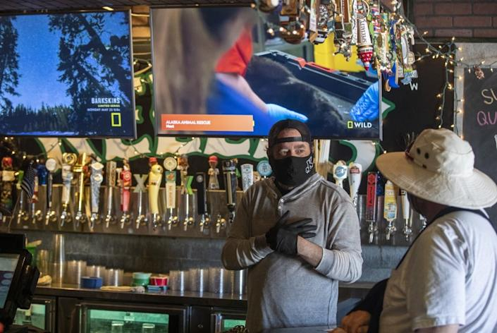 """Jim Rafferty, owner of Kelly's Korner — one of Orange County's best-known sports bars — chats with a regular on May 16 in Placentia. <span class=""""copyright"""">(Brian van der Brug / Los Angeles Times)</span>"""