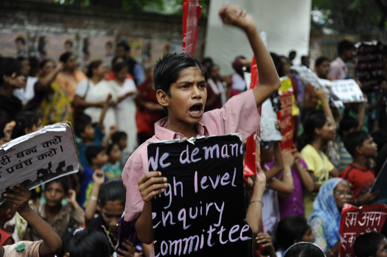 """An Indian boy shouts slogans, holding a placards during a protest organized by non-governmental organization Bachpan Bachao Andolan, or Save Childhood Movement, against the death of schoolchildren after eating free midday meal served at a school, in New Delhi, India, Saturday, July 20, 2013. Police say samples of cooking oil and leftover food taken from an Indian school where 23 children died after eating lunch this past week were contaminated with """"very toxic"""" levels of an agricultural pesticide. (AP Photo/Altaf Qadri)"""