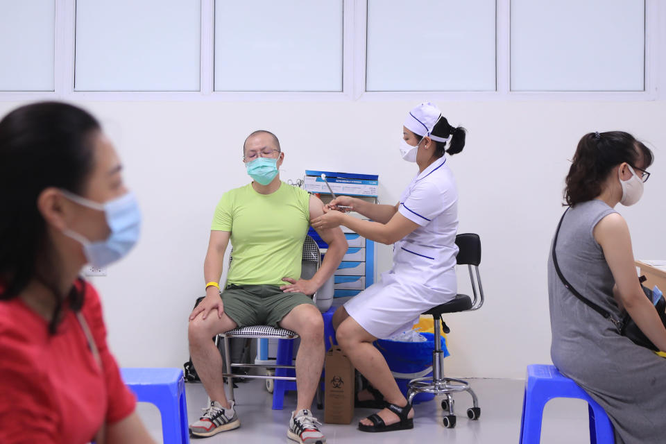 A man receives a shot of AstraZeneca COVID-19 vaccine in Hanoi, Vietnam Sunday, June 27, 2021. Vietnam is ramping up the vaccination program against COVID-19 as new cases increase. (AP Photo/Hau Dinh)