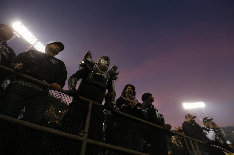 Fans watch as players warm up for an NFL football game between the Oakland Raiders and the Los Angeles Chargers in Oakland, Calif., Thursday, Nov. 7, 2019. (AP Photo/D. Ross Cameron)