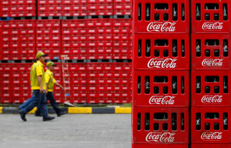 FILE PHOTO: Workers walk at PT Coca-Cola Amatil Indonesia's factory in Cibitung