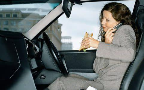 Businesswoman eating lunch in car, using mobile phone - Daly & Newton/Getty Images
