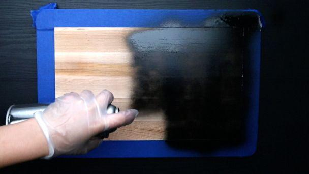 PHOTO: Chalkboard spray paint being applied to wooden cutting board. (ABC News)