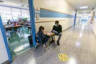A teacher's assistant helps a first grade student with her work during the coronavirus outbreak in the hallway of School 16, Tuesday, Oct. 20, 2020, in Yonkers, N.Y. (AP Photo/Mary Altaffer)