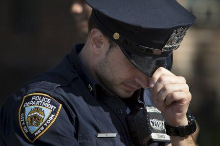 A New York Police officer bows his head near the scene where the shooting of officer Randolph Holder occurred in the Manhattan borough of New York, October 21, 2015. REUTERS/Andrew Kelly