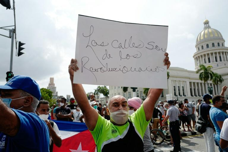 """A pro-government counter-demonstrator holds a signal that reads """"The streets belong to the revolutionaries"""" amid demonstrations against the government of Cuban President Miguel Diaz-Canel in Havana on July 11, 2021"""