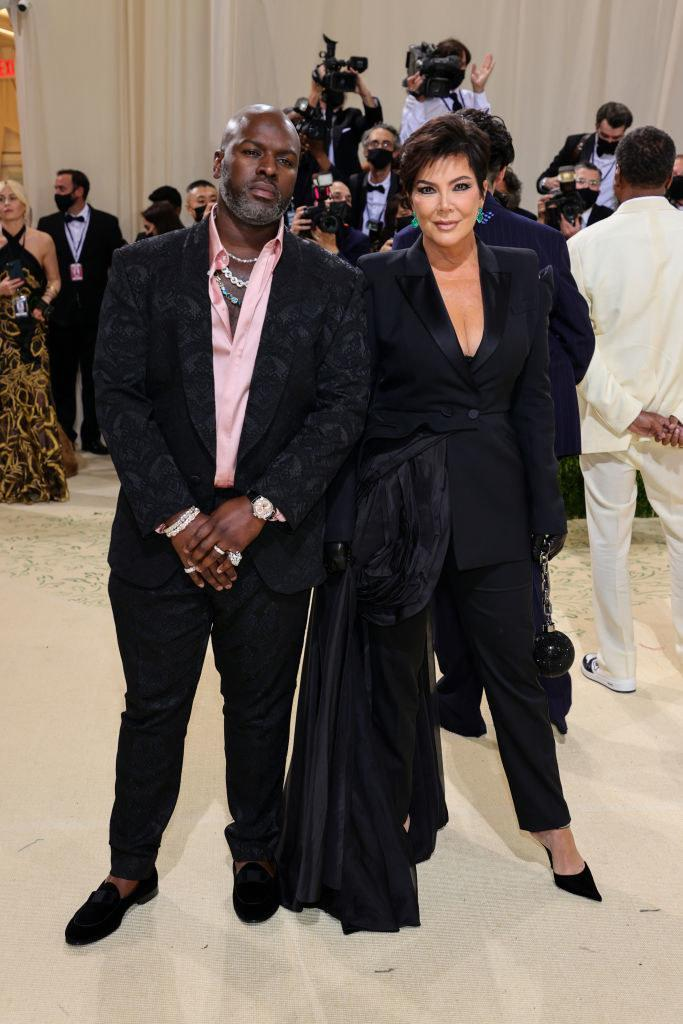 Kris Jenner wears a dark suit with a short train wrapped around her waist and Corey Gamble wears a brightly colored button up shirt under a dark blazer and matching slacks