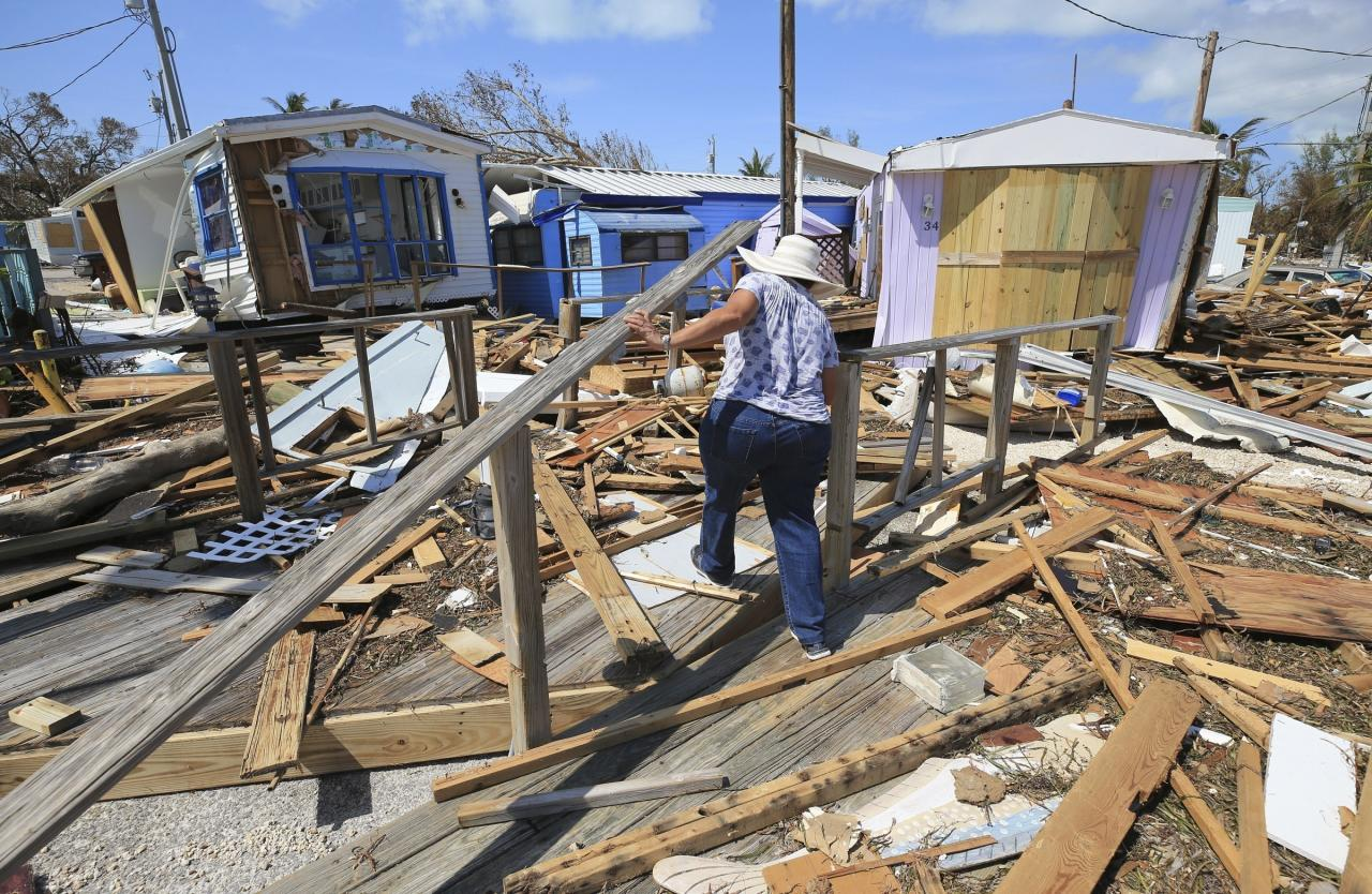 <p>Mirta Mendez walks through the debris at the Seabreeze trailer park along the Overseas Highway in the Florida Keys on Sept. 12, 2017. Florida is cleaning up and embarking on rebuilding from Hurricane Irma, one of the most destructive hurricanes in its history. (Photo: Al Diaz/Miami Herald/AP) </p>