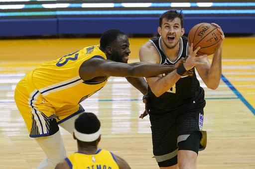 Sacramento Kings forward Nemanja Bjelica, right, drives against Golden State Warriors forward Draymond Green during the first half of an NBA basketball game in San Francisco, Monday, Jan. 4, 2021. (AP Photo/Jeff Chiu)