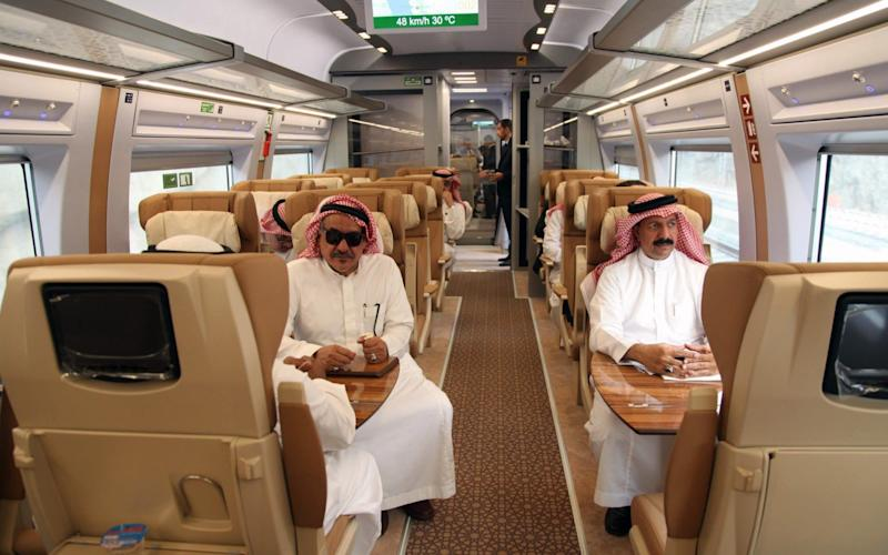 Saudi officials sitting in a high-speed train, ahead of their trip, at a station in Saudi Arabia's holy city of Mecca - AFP