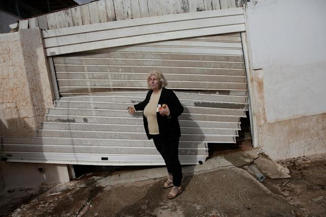 <p>Local Konstantina Louka stands next to her destroyed garage entrance following a heavy rainfall in the town of Mandra, Greece, Nov. 15, 2017. (Photo: Alkis Konstantinidis/Reuters) </p>
