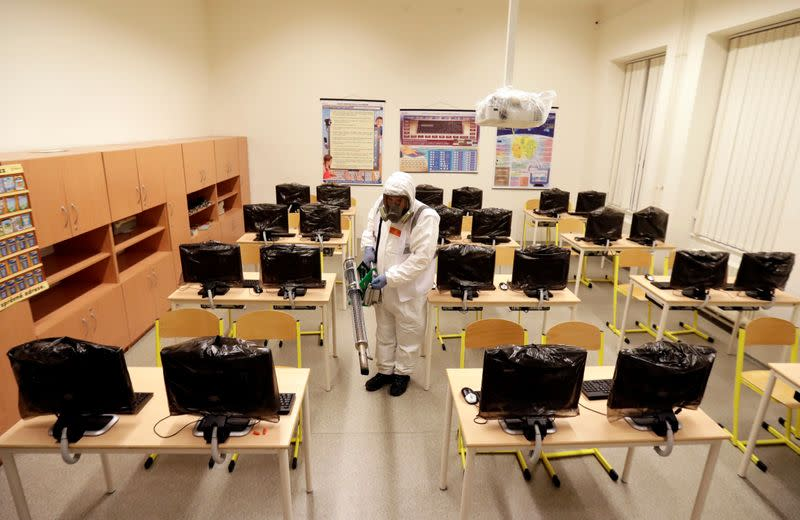 FILE PHOTO: A worker in a protective suit disinfects a classroom in Prague