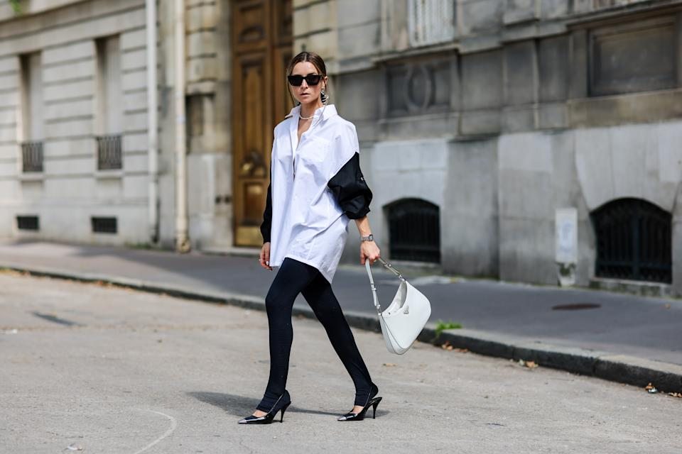 PARIS, FRANCE - AUGUST 15: Julia Comil wears an oversized cotton white and black shirt with triangle Prada logo and zipped by Prada, black leggings, a Cleo white patent leather shoulder bag with triangle logo by Prada, blade slingback pointed pumps shoes in black patent leather with silver metallic tip by Saint Laurent, cat eye black sunglasses Saint Laurent, a Prada hair barrette, 2000s hairstyle pulled back hair with tiny strands in the front, a maxi scrunchie, a pearl necklace, on August 15, 2021 in Paris, France. (Photo by Edward Berthelot/Getty Images)