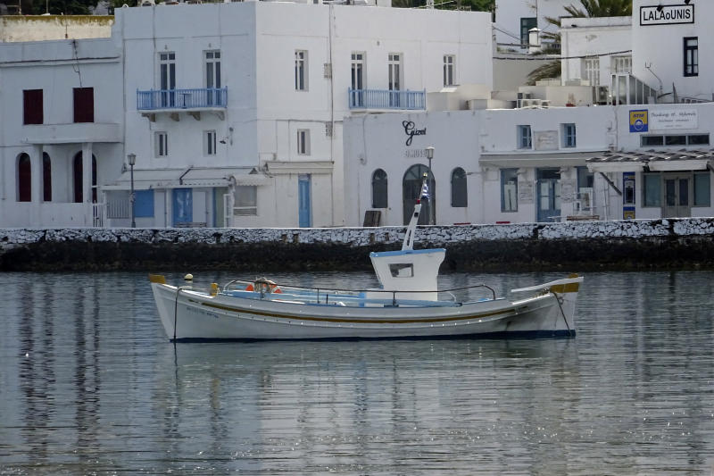 In this Tuesday, June 9, 2020, photo, a fishing boat is anchored in front of the main walkway on the Greek island of Mykonos, Greece. Business owners and locals officials on the Greek holiday island of Mykonos, a popular vacation spot for celebrities, club-goers, and high rollers, say they are keen to reopen for business despite the risks of COVID-19 posed by international travel. Greece will officially launch its tourism season Monday, June 15, 2020 after keeping the country's infection rate low. (AP Photo/Derek Gatopoulos)