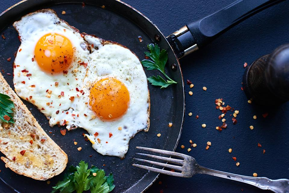 Fried eggs and slice of bread on pan