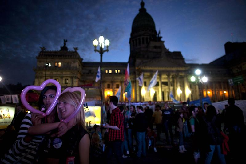 Transvestites pose for a picture with heart shaped balloons outside Congress in Buenos Aires, Argentina, Wednesday, May 9, 2012. Argentina's Congress is set to approve on Wednesday the Gender Identity Law, which allows citizens to change their gender in public records, including birth certificates and national identity cards. (AP Photo/Natacha Pisarenko)
