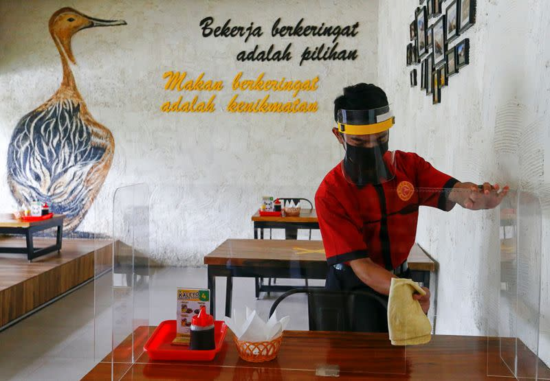 A worker wearing a face shield and a mask wipes a protective screen on a table at a restaurant, in Jakarta
