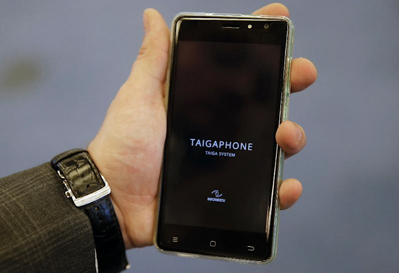 A man holds a TaigaPhone, a brand new smartphone created by InfoWatch Group, during a presentation in Moscow on September 22, 2017