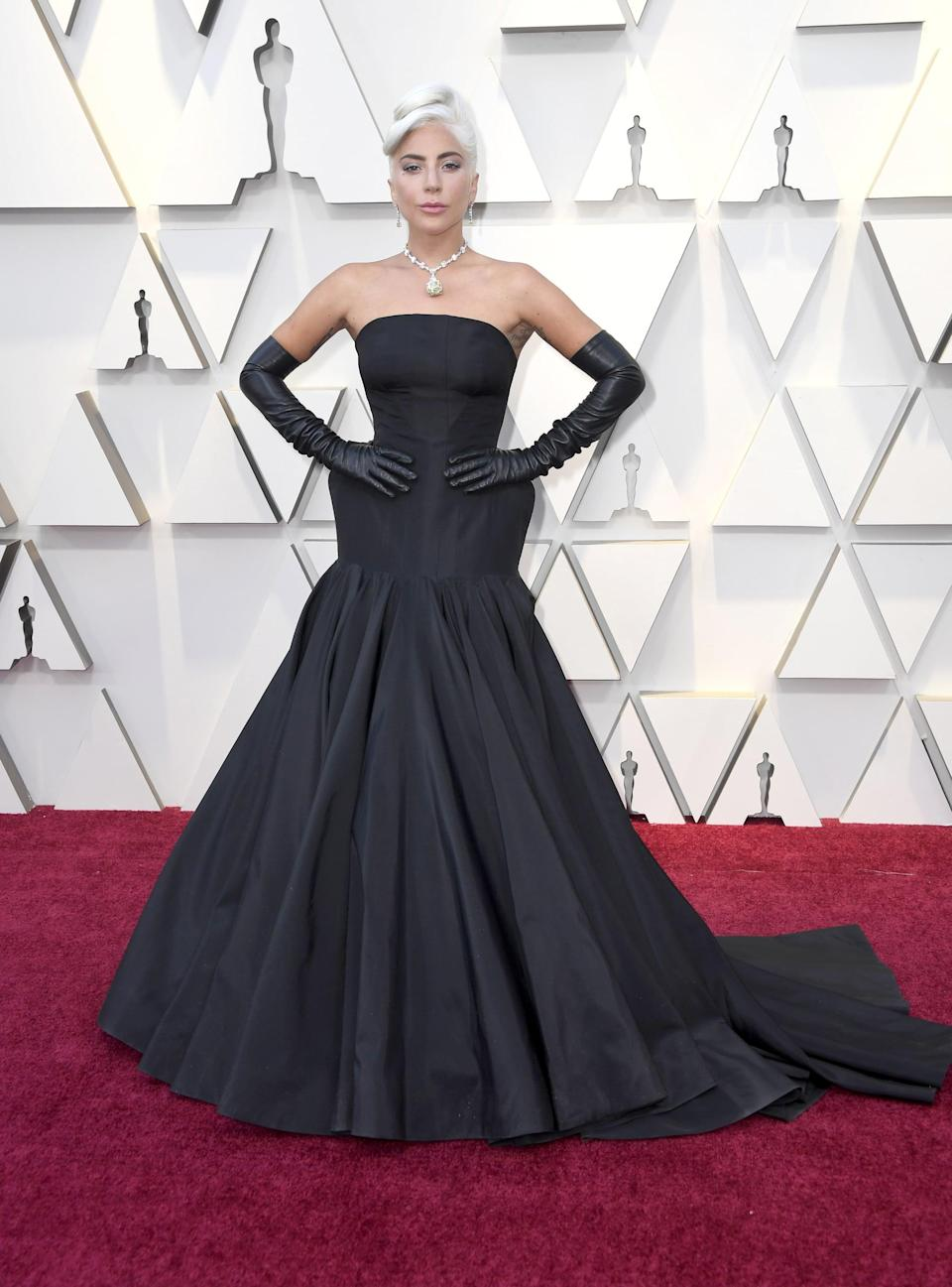 """<p>The <strong>A Star Is Born</strong> actress <a href=""""https://www.popsugar.com/fashion/Lady-Gaga-Dress-2019-Oscars-45832034"""" class=""""link rapid-noclick-resp"""" rel=""""nofollow noopener"""" target=""""_blank"""" data-ylk=""""slk:attended the 2019 Oscars wearing a black strapless Alexander McQueen gown"""">attended the 2019 Oscars wearing a black strapless Alexander McQueen gown</a>, complete with glam gloves.</p>"""
