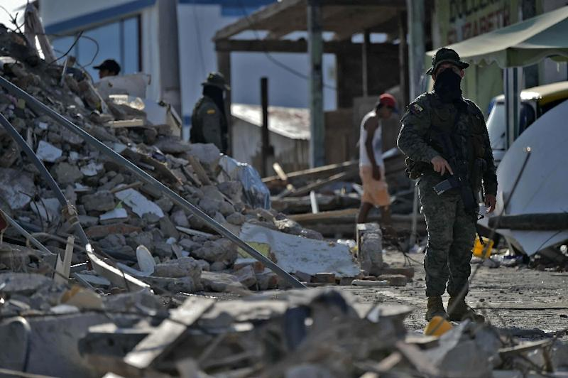 A soldier stands guard as rescuers search for victims in Pedernales, Ecuador on April 19, 2016 (AFP Photo/Rodrigo Buendia)