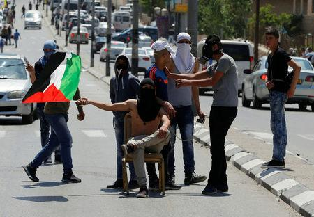 A protester waves a Palestinian flag as he sits on a chair during clashes with Israeli troops following a protest in solidarity with Palestinian prisoners held by Israel, in the West Bank town of Bethlehem April 17, 2017. REUTERS/Ammar Awad