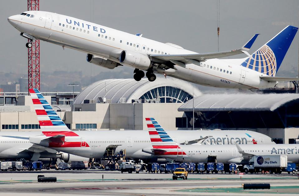 LOS ANGELES, CALIFORNIA - OCTOBER 01: A United Airlines plane takes off above American Airlines planes on the tarmac at Los Angeles International Airport (LAX) on October 1, 2020 in Los Angeles, California. United Airlines and American Airlines are set to start furloughing 32,000 employees today after negotiations for a new coronavirus aid package failed in Washington.  (Photo by Mario Tama/Getty Images)