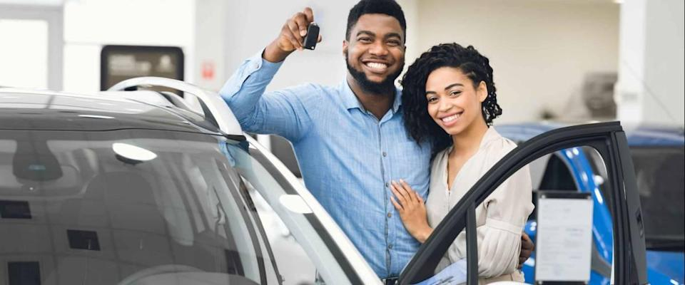Cheerful Couple Standing Near New Car Showing Key Smiling To Camera In Auto Dealership Center.