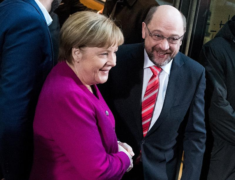 German Chancellor Angela Merkel, leader of the Christian Democratic Union, greets Martin Schulz, leader of Germany's social democratic SPD party, as they arrive for a meeting on January 7, 2018 in Berlin