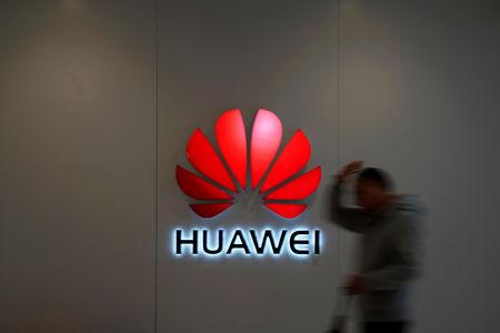 A man walks by a Huawei logo at a shopping mall in Shanghai, China December 6, 2018. REUTERS/Aly Song/Files