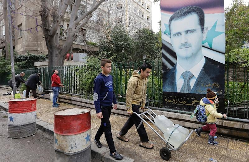 Syrians fill plastic containers with water at a public fountain in the capital Damascus on January 3, 2017 (AFP Photo/LOUAI BESHARA)