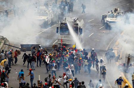 Opposition supporters clash with riot police during a rally against President Nicolas Maduro in Caracas, Venezuela, May 3, 2017.  REUTERS/Christian Veron