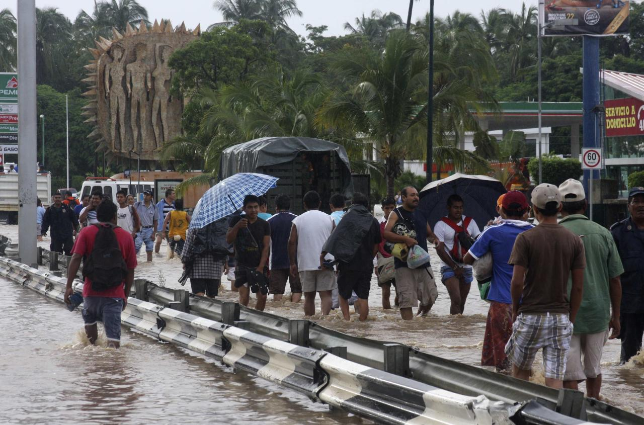 People walk through flooded streets in Acapulco