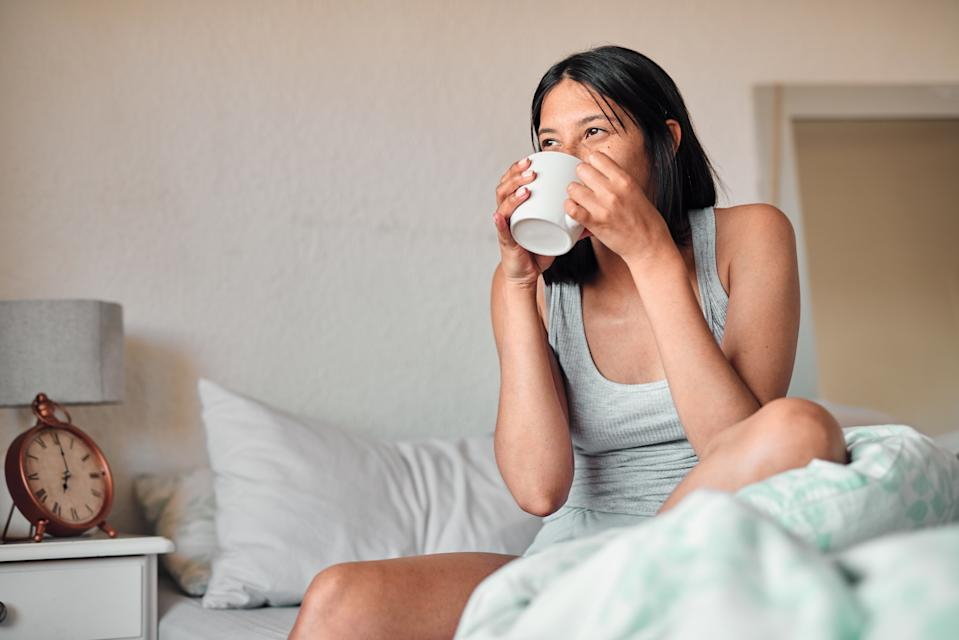 Shot of a young woman enjoying a relaxing cup of coffee in bed at home