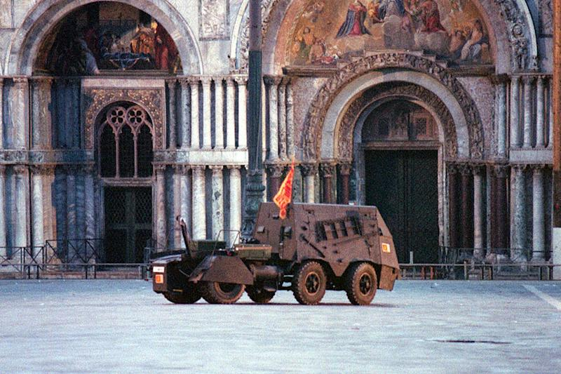 FILE - In this Friday, May 9, 1997 file photo, the mock armored car brought to St. Mark's square by the self-proclaimed Venetian separatists who had occupied the bell tower in the heart of Venice. In background the facade of St. Mark's Basilica. Italian special operations units on Wednesday, April 2, 2014, arrested 24 secessionists who were allegedly planning a violent campaign aimed at making the wealthy northeastern Veneto region independent. Police said in a statement that the group had built an armored vehicle that they intended to deploy in St. Mark's Square in Venice — reminiscent of a 7 ½-hour takeover of the piazza's famed bell tower by secessionists in 1997. TV footage showed the so-called tank was a tractor that had been armed in some fashion. Italian media reported that the secessionists intended to deploy the vehicle on the eve of European Parliamentary elections in May, which will be a measure of growing anti-Europe sentiment arising from harsh austerity measures to fight the economic crisis. (AP Photo/Franco Proietti, File)