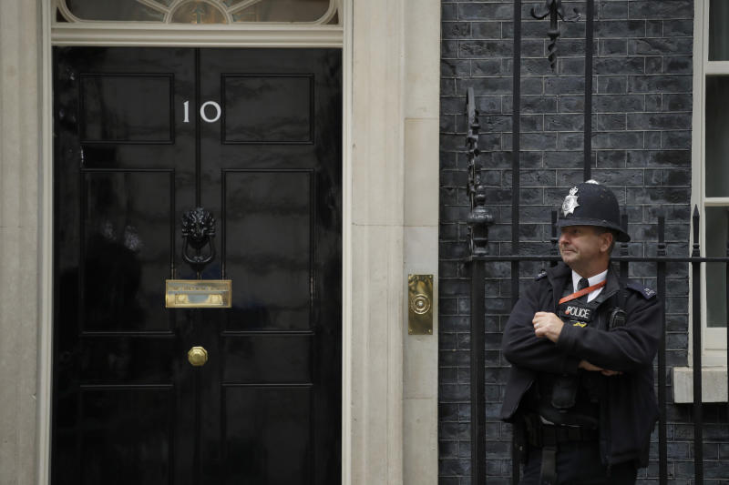A police officer stands guard outside the door of 10 Downing Street in London, Friday, June 7, 2019. Prime Minister Theresa May is stepping down as Britain's Conservative party leader later Friday, defeated by her failure to take Britain out of the European Union on schedule. She will remain as prime minister for a few weeks while the party picks a successor. (AP Photo/Matt Dunham)
