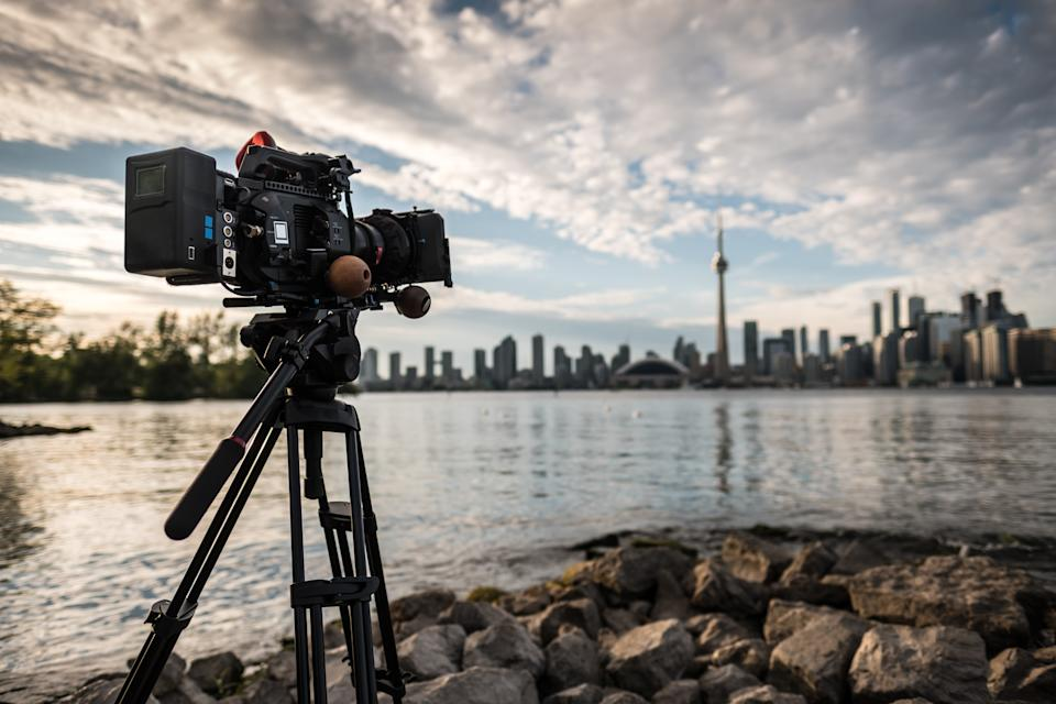 Toronto, Ontario, Canada. Professional 4K Video camera on tripod shooting time lapse of downtown panorama in sunset. Rocky beach of Toronto Island. Shallow depth of field with point of the focus on rear of the camera.
