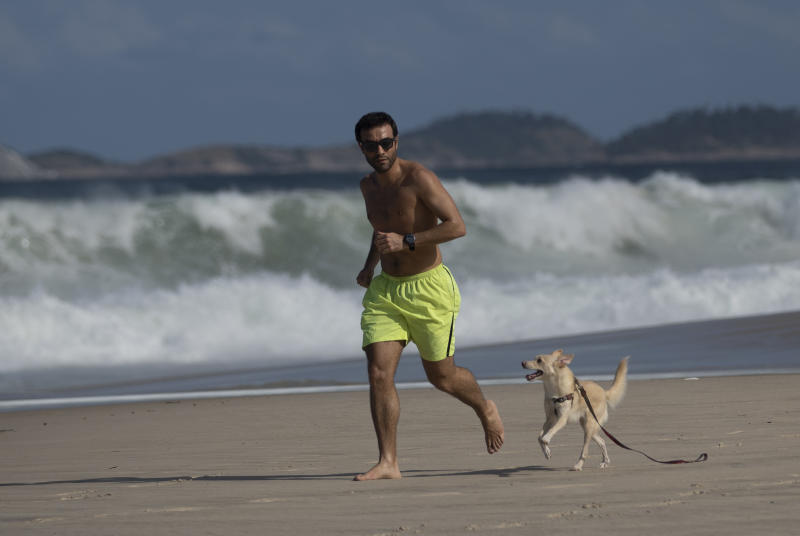 A man runs with his dog on the Copacabana beach during the new coronavirus pandemic in Rio de Janeiro, Brazil, Thursday, July 2, 2020. Rio de Janeiro authorities have begun to ease the city's lockdown amid the growing COVID-19 pandemic. (AP Photo/Silvia Izquierdo)