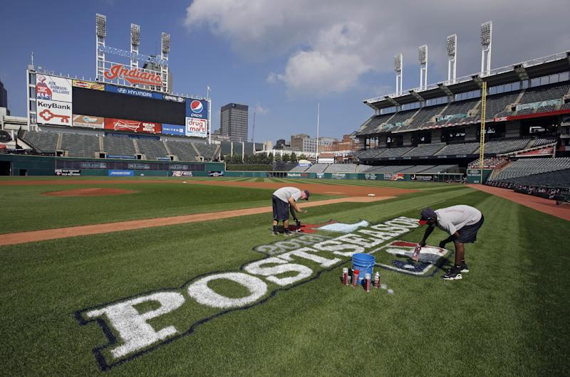 Matt Guden, center, and Marcus Hunter paint a postseason logo on the infield at Progressive Field in Cleveland Tuesday, Oct. 1, 2013. The Cleveland Indians host the Tampa Bay Rays in the AL wild-card baseball game Wednesday night, with the winner advancing to the divisional series against the Boston Red Sox. (AP Photo/Mark Duncan)