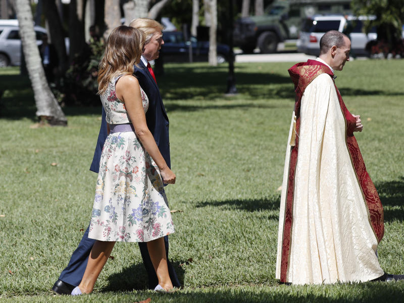 President Donald Trump with first lady Melania Trump, walk behind the Rev. James R. Harlan, right, as they arrive for Easter services at Episcopal Church of Bethesda-by-the-Sea, Sunday, April 21, 2019, in Palm Beach, Fla. (AP Photo/Pablo Martinez Monsivais)