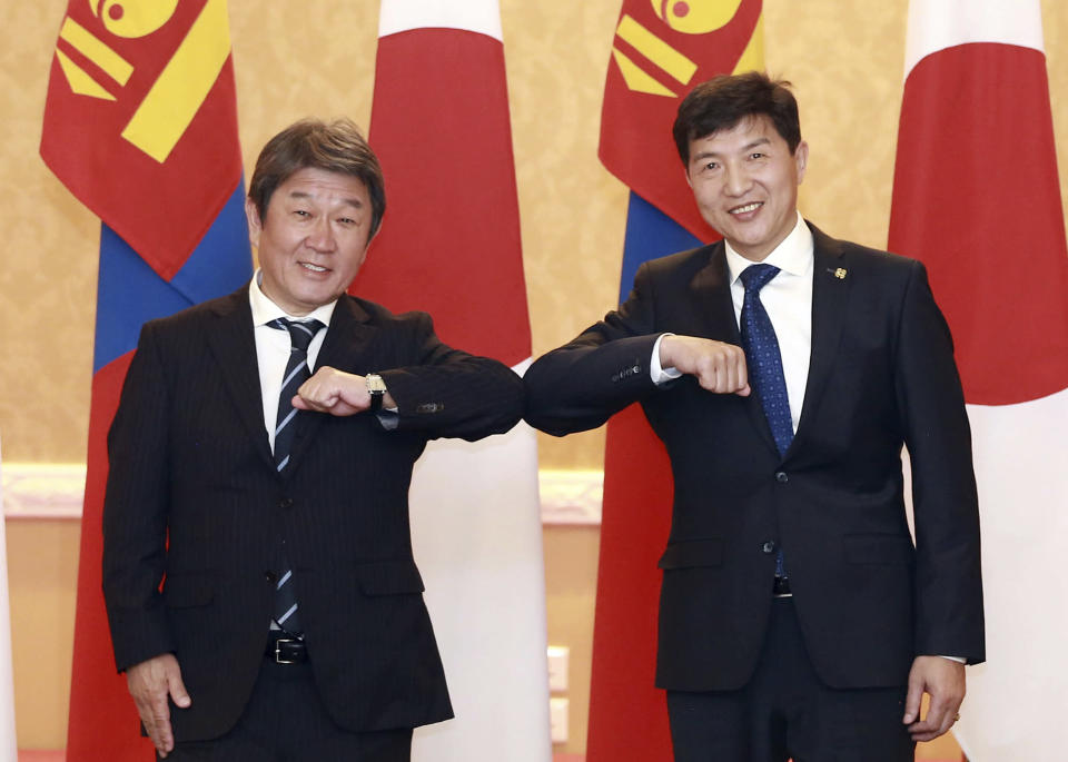 In this photo provided by Ministry of Foreign Affairs of Japan, Japanese Foreign Minister Toshimitsu Motegi, left, and Mongolia's Foreign Minister Nyamtseren Enkhtaivan pose for a photo during their meeting in Ulaanbaatar, Mongolia, Friday, Oct. 9, 2020. (Ministry of Foreign Affairs of Japan via AP)