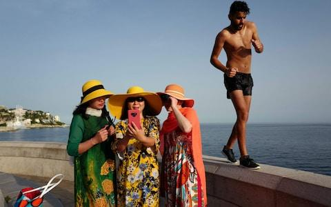 A man walks by as tourists take selfies on the French Riviera city of Nice on June 24, 2019, as temperatures soar to 33 degrees Celsius. - Credit: VALERY HACHE/AFP