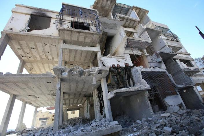 Members of the Syrian pro-government forces stand in a destroyed building in the strategic town of Salma, in Latakia province, on January 15, 2016, following its recapture from rebel fighters (AFP Photo/Youssef Karwashan)
