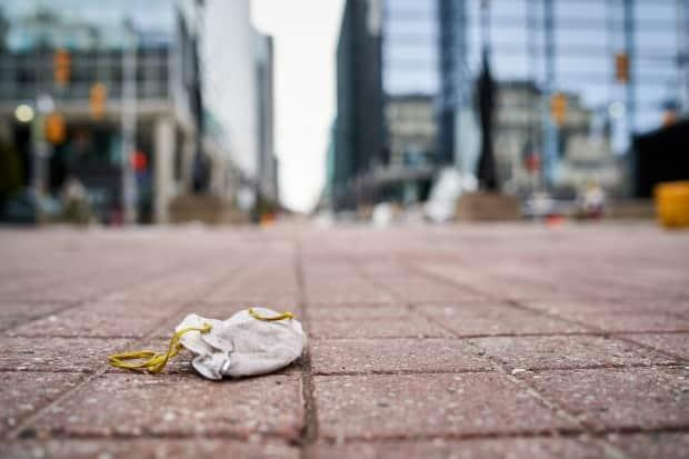 A mask is seen disposed in downtown Ottawa in March 2020, the month COVID-19 was declared a pandemic. Canadians need to wait a little longer to see mask rules be loosened, according to an epidemiologist. (David Richard/CBC - image credit)