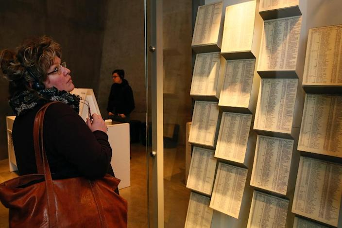 A woman looks at copies of facsimiles of Oskar Schindler's lists displayed at the Yad Vashem Holocaust memorial museum in Jerusalem, on March 4, 2015 (AFP Photo/Gali Tibbon)