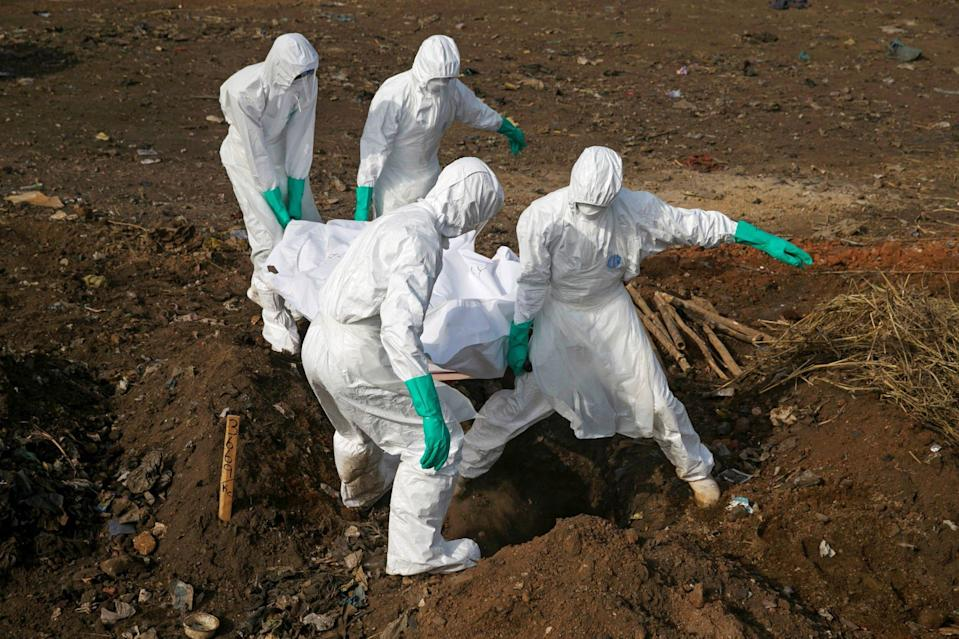 Health workers carry the body of a suspected Ebola victim for burial at a cemetery in Freetown, Sierra Leone, December 21, 2014. Photo: Reuters