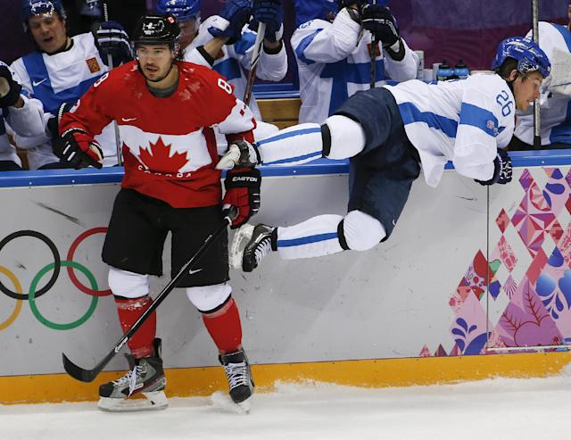 Canada defenseman Drew Doughty, left, avoids Finland forward Jarkko Immonen in the first period of a men's ice hockey game at the 2014 Winter Olympics, Sunday, Feb. 16, 2014, in Sochi, Russia. (AP Photo/Julio Cortez)