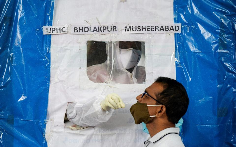 A health worker collects a swab from a resident at a makeshift free COVID-19 coronavirus testing booth in Hyderabad - NOAH SEELAM/AFP